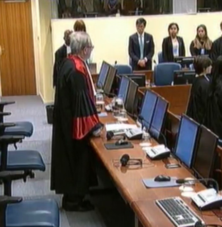 Video feed snapshot of a status conference with the President, Judge Carmel Agius, as presiding judge.